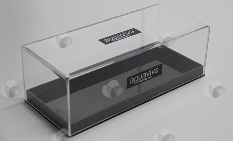 Caixa expositora em acrílico com base preta e tampa transparente, personalizada com adesivagem