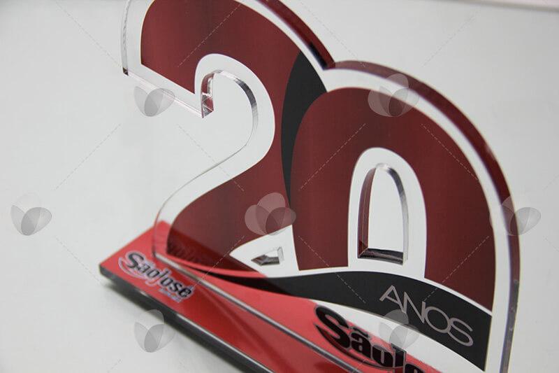 Troféu em acrílico comemorativo de aniversário de empresa, com recorte que reproduz o número 20, personalizado com adesivagem de fundo vermelho
