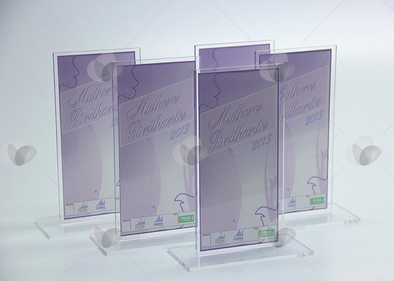 """Premiações no modelo """"T"""" fabricadas em acrílico e personalizadas com adesivagem com cor predominante lilás para homenagear mulheres"""