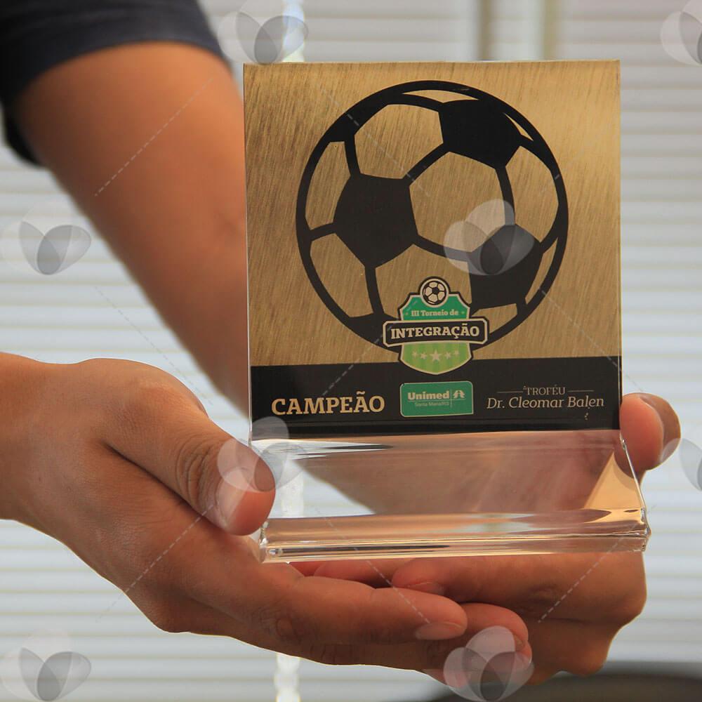 Troféu em acrílico cristal, feito no modelo Z, personalizado com adesivagem espelhada com fundo dourado.